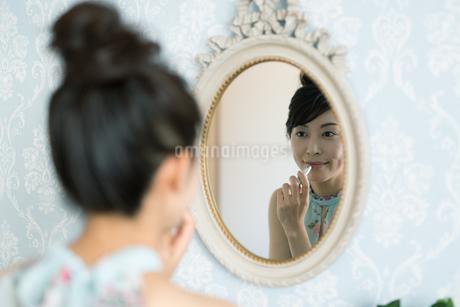 鏡の前で口紅をつける女性の写真素材 [FYI01776248]