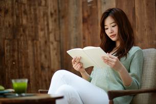 カフェで読書する女性の写真素材 [FYI01776429]