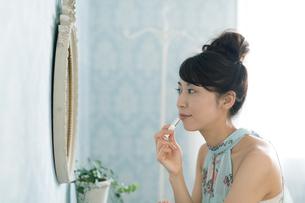 鏡の前で口紅をつける女性の写真素材 [FYI01776437]