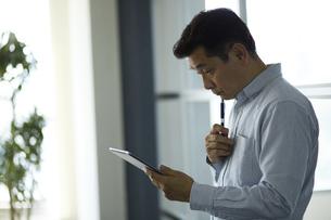 タブレットPCを使うビジネスマンの写真素材 [FYI01776511]