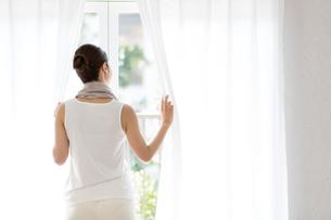 窓の前の若い女性の写真素材 [FYI01776537]