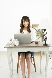 机でパソコンを使う若い女性の写真素材 [FYI01776542]