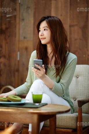カフェで携帯電話を使う女性の写真素材 [FYI01776560]