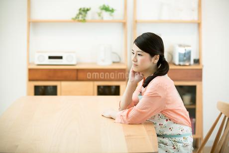 リビングでエプロン姿の若い主婦の写真素材 [FYI01776627]