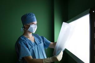 レントゲン写真を見る手術着を着た女医の写真素材 [FYI01776730]