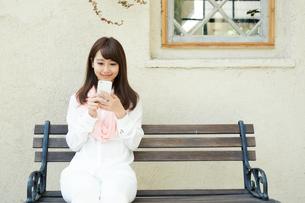 庭のベンチで携帯電話を使う女性の写真素材 [FYI01776772]