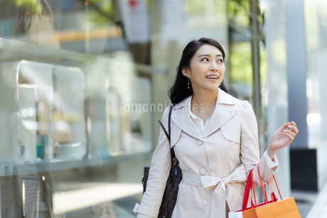 紙袋を持つトレンチコートの女性の写真素材 [FYI01776839]