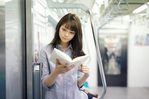 電車で読書する若い女性の写真素材 [FYI01776964]