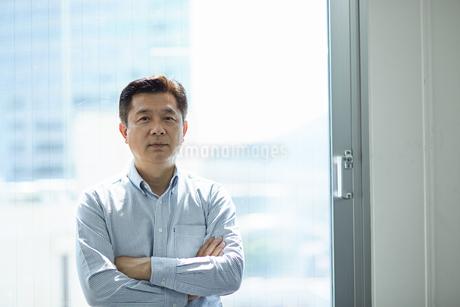窓際で腕組みするビジネスマンの写真素材 [FYI01776979]