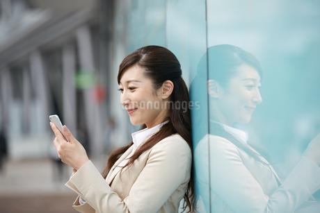 屋外で携帯電話を使う女性の写真素材 [FYI01777034]
