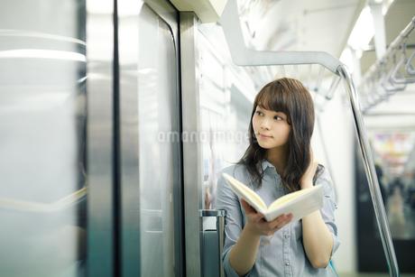 電車で読書する若い女性の写真素材 [FYI01777123]