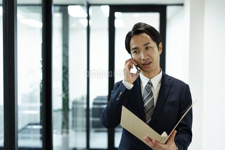 携帯電話を使うビジネスマンの写真素材 [FYI01777143]