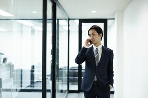 携帯電話を使うビジネスマンの写真素材 [FYI01777156]