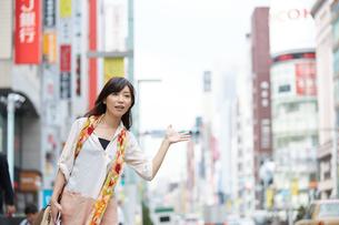 タクシーを呼ぶ爽やかな女性の写真素材 [FYI01777214]