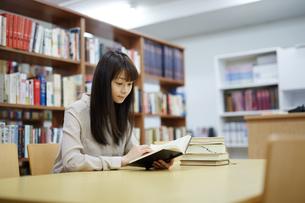 図書館で本を読む若い女性の写真素材 [FYI01777218]