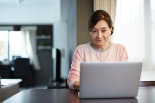 リビングでパソコンを使う女性の写真素材 [FYI01777260]