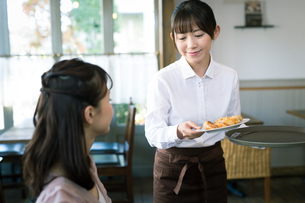 カフェで働く女性とお客の写真素材 [FYI01777275]