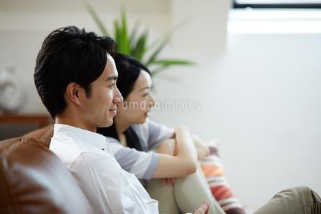 ソファに座る若い夫婦の写真素材 [FYI01777359]