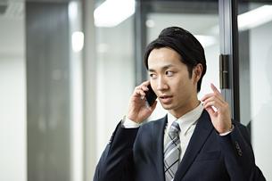携帯電話で真剣に話すビジネスマンの写真素材 [FYI01777439]