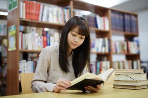 図書館で本を読む若い女性の写真素材 [FYI01777531]