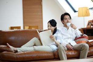 ソファで寛ぐ若い夫婦の写真素材 [FYI01777682]