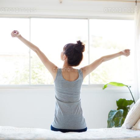 ベッドに腰掛ける女性の写真素材 [FYI01777775]
