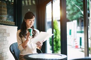 カフェテラスで読書する女性の写真素材 [FYI01777808]