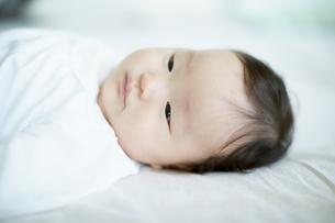 ベッドに寝転ぶ赤ちゃんの写真素材 [FYI01777953]