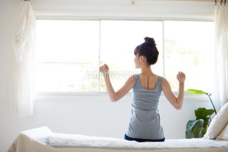 ベッドに腰掛ける女性の写真素材 [FYI01778079]
