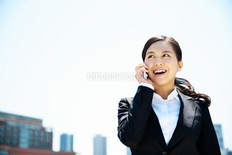 屋外で携帯電話を使うビジネスウーマンの写真素材 [FYI01778437]