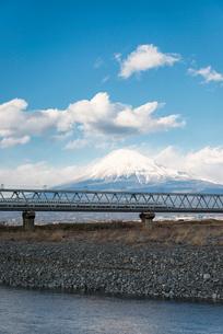 富士川の鉄道橋を走行する新幹線と富士山の写真素材 [FYI01782444]