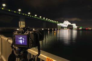 若洲海浜公園にて東京ゲートブリッジを撮影中の三脚に備え付けられたカメラの写真素材 [FYI01782637]