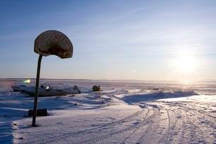 雪の大地に昇る太陽とバスケットゴールの写真素材 [FYI01782753]
