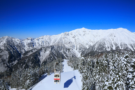 新穂高ロープウェイと雪景色の北アルプスの写真素材 [FYI01795004]