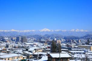 雪化粧した北アルプスと飛騨高山の街並みの写真素材 [FYI01795076]
