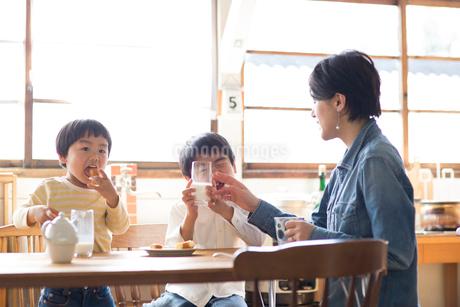 キッチンのテーブルでおやつを食べる兄弟と母親の写真素材 [FYI01795217]