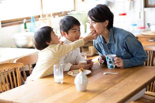 キッチンのテーブルでおやつを食べる兄弟と母親の写真素材 [FYI01795221]