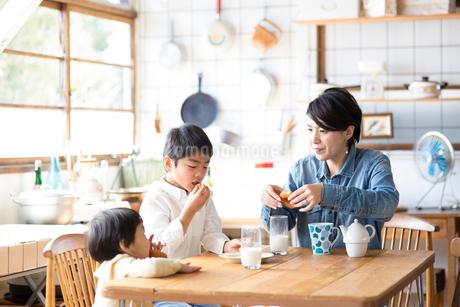 キッチンのテーブルでドーナツを食べる兄弟と母親の写真素材 [FYI01795246]
