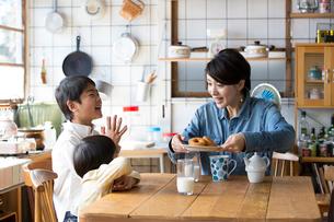キッチンのテーブルでドーナツを食べる兄弟と母親の写真素材 [FYI01795249]