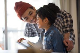 本を読む小学生の女の子とそれを見ている父親の写真素材 [FYI01795302]