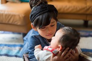 あかちゃんの妹を抱きながら見つめる小学生の姉の写真素材 [FYI01795335]