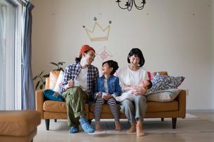 リビングのソファーに座ってくつろぐ家族の写真素材 [FYI01795380]