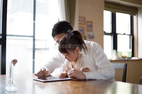 タブレットを使う女の子と父親の写真素材 [FYI01795384]