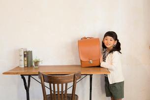 机の上に置いてあるランドセルと小学生の女の子の写真素材 [FYI01795404]