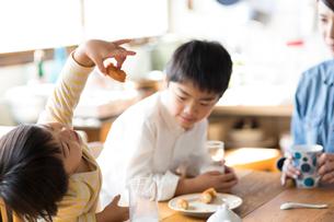キッチンのテーブルでおやつを食べる兄弟と母親の写真素材 [FYI01795428]