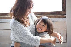 笑顔で抱き合う母親と娘の写真素材 [FYI01795429]