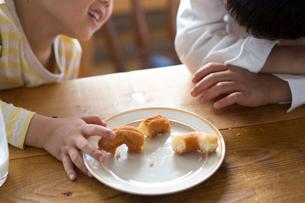 キッチンのテーブルでドーナツを食べる子どもの手の写真素材 [FYI01795433]