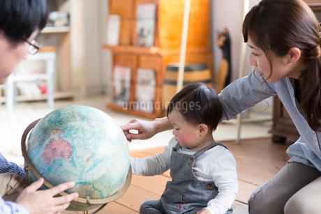 地球儀で遊ぶ赤ちゃんと両親の写真素材 [FYI01795464]