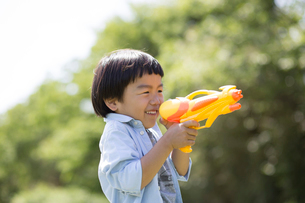 水鉄砲を持って狙いを定める男の子の写真素材 [FYI01795468]