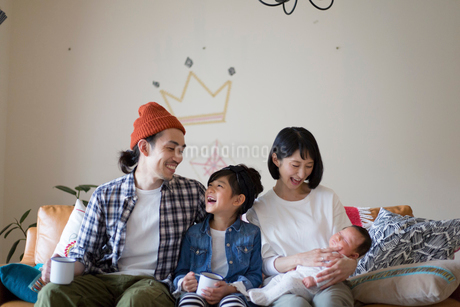 リビングのソファーに座ってくつろぐ家族の写真素材 [FYI01795469]